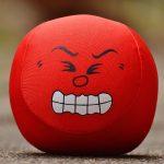 Roter Stressball mit wütendem Gesicht