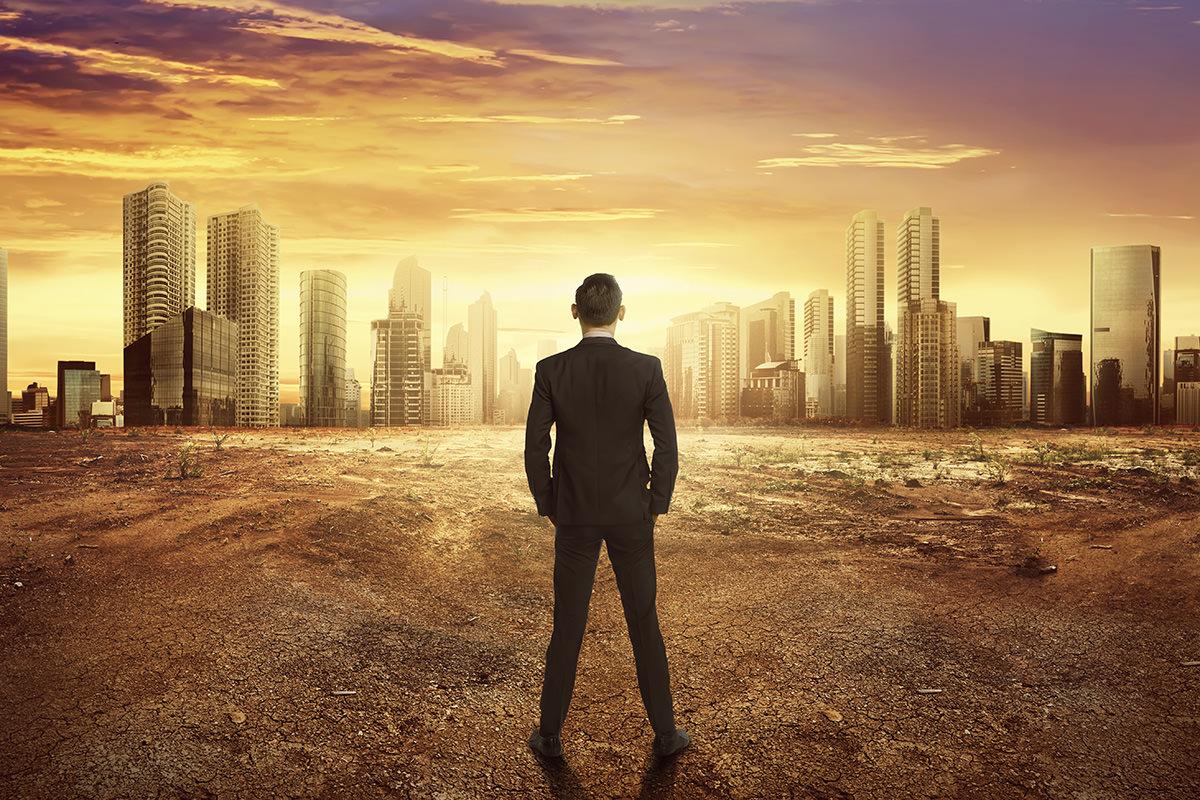 Mann von hinten mit Blick auf Skyline in der Morgensonne