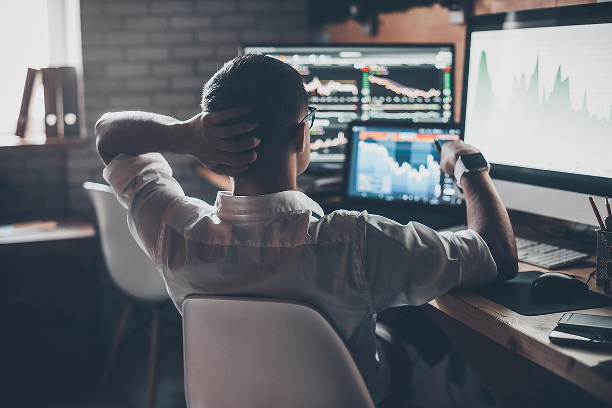 Blick auf Mann von hinten am Schreibtisch mit Graphen auf den Monitoren