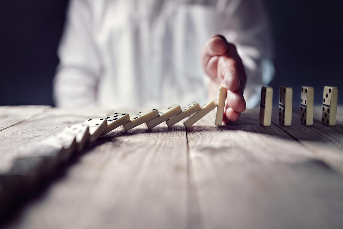 Mann stoppt umfallende Dominosteine mit der Hand