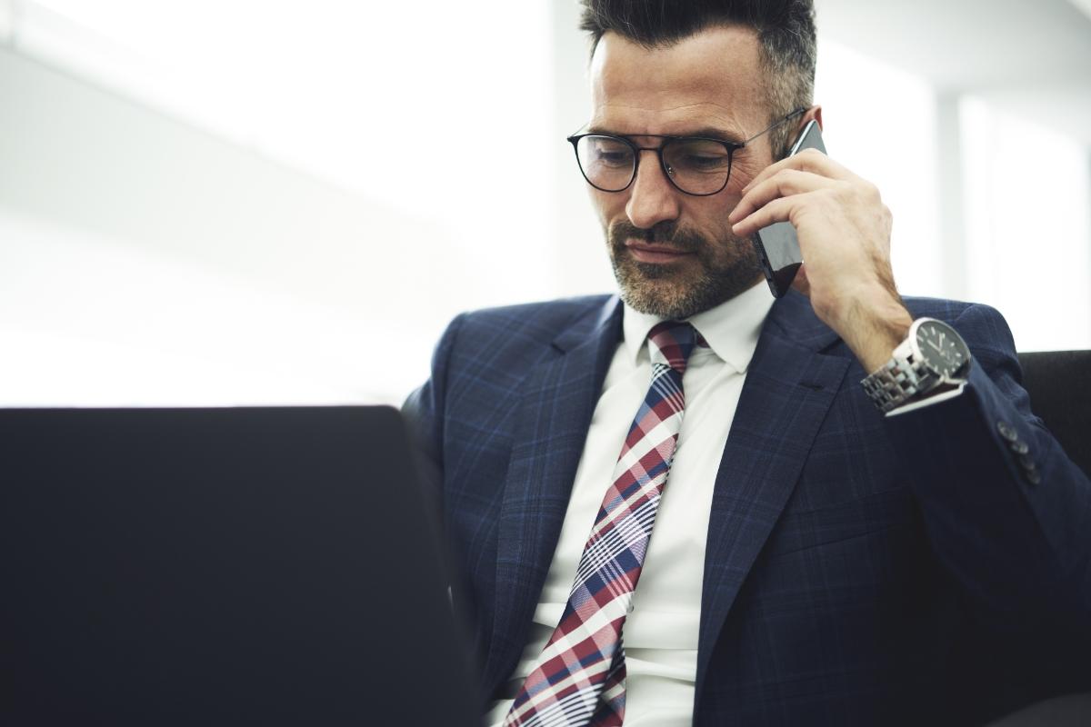 Manager bei der Arbeit am Laptop mit Handy am Ohr