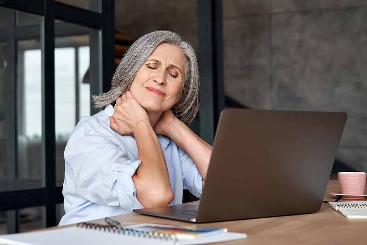 Frau vor Laptop mit Nackenschmerzen