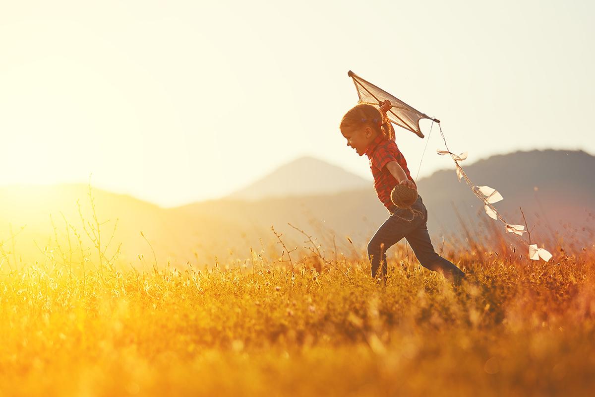 Kind beim Dachensteigenlassen im Sonnenuntergang