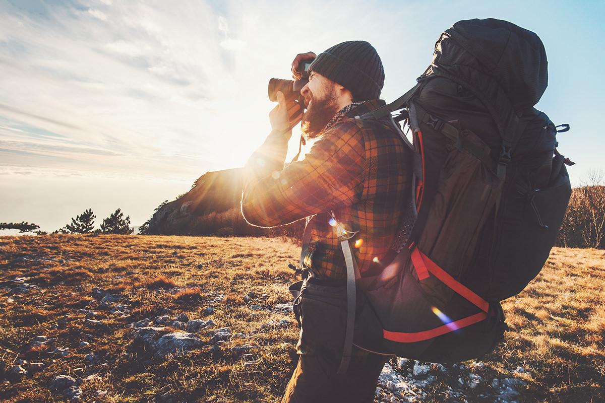 Mann in der Natur mit Backpacker-Rucksack macht Foto bei Sonnenuntergang