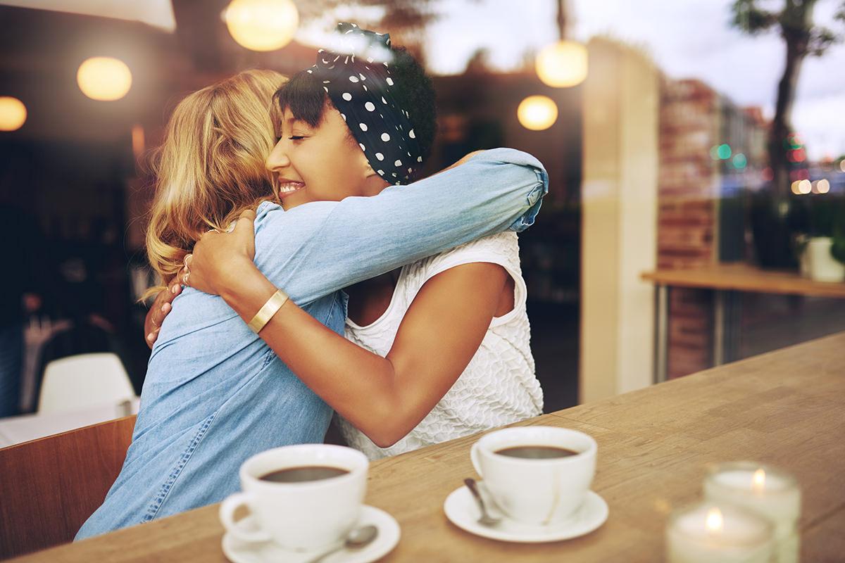 Zwei Frauen umarmen sich im Café bei einer Tasse Kaffee