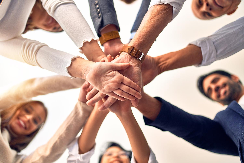 Gruppe von Menschen legen die Hände aufeinander - Teambuilding