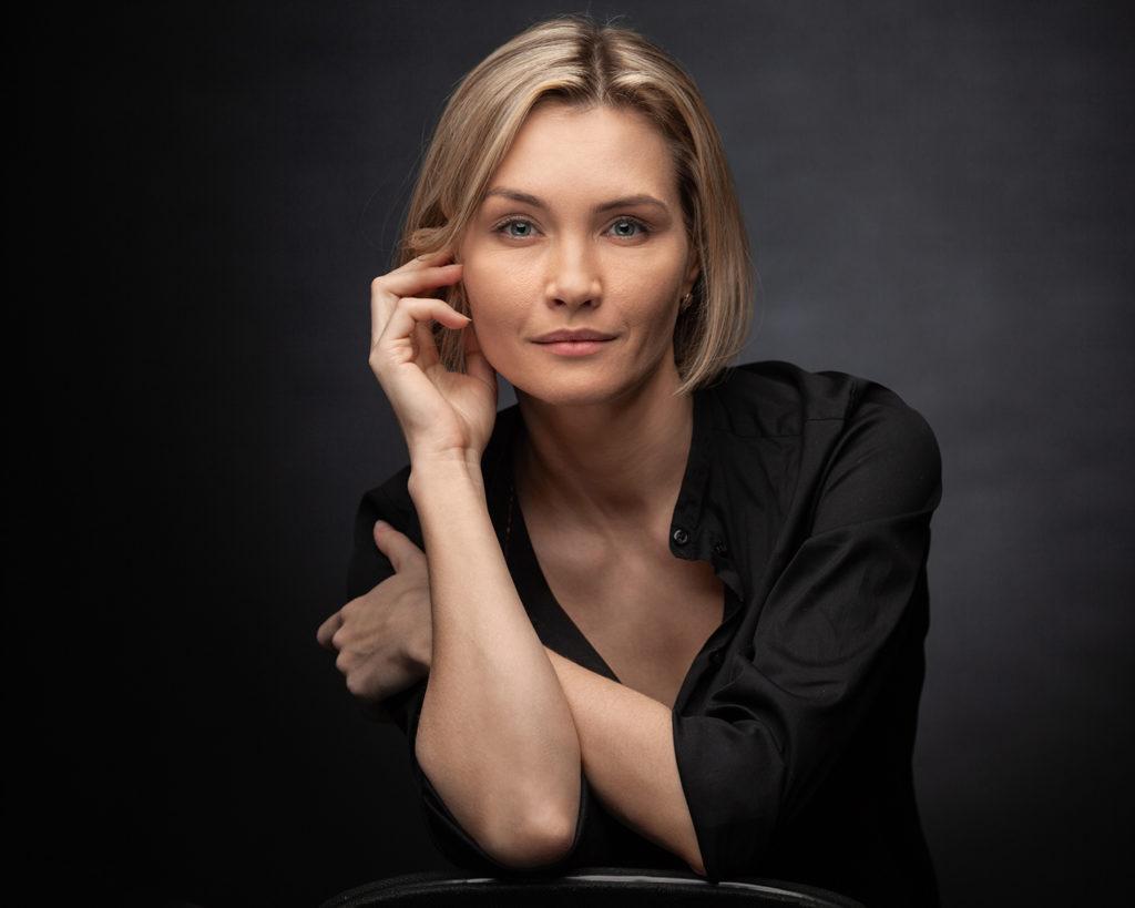 Blonde Frau mit schwarzer Bluse.