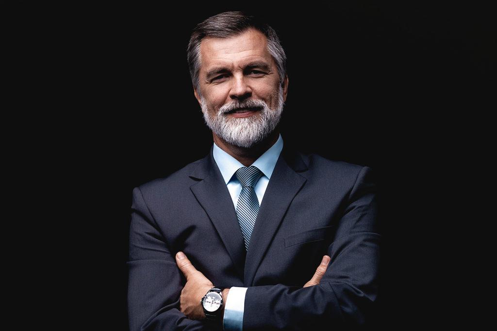 Mann mit grauem Bart im Anzug