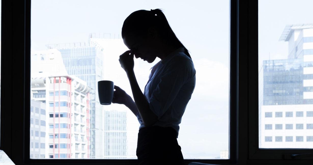 Silhouette einer gestressten Frau steht mit Kaffeetasse in der Hand vor einem Fenster, während sie sich mit der Hand an die Stirn fasst.